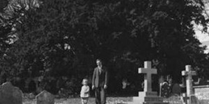 Image: Man and small girl in front of yew tree, taken by George Bennett, 1930s.
