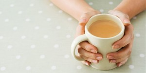 Hands clasping mug of hot tea