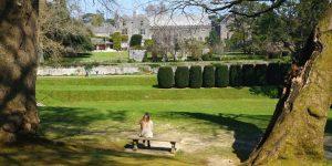 Woman on bench overlooking the Tiltyard at Dartington Hall